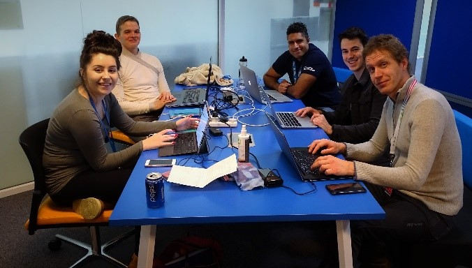Hackathon Shipley Chelsea and team sitting together at a desk with laptops