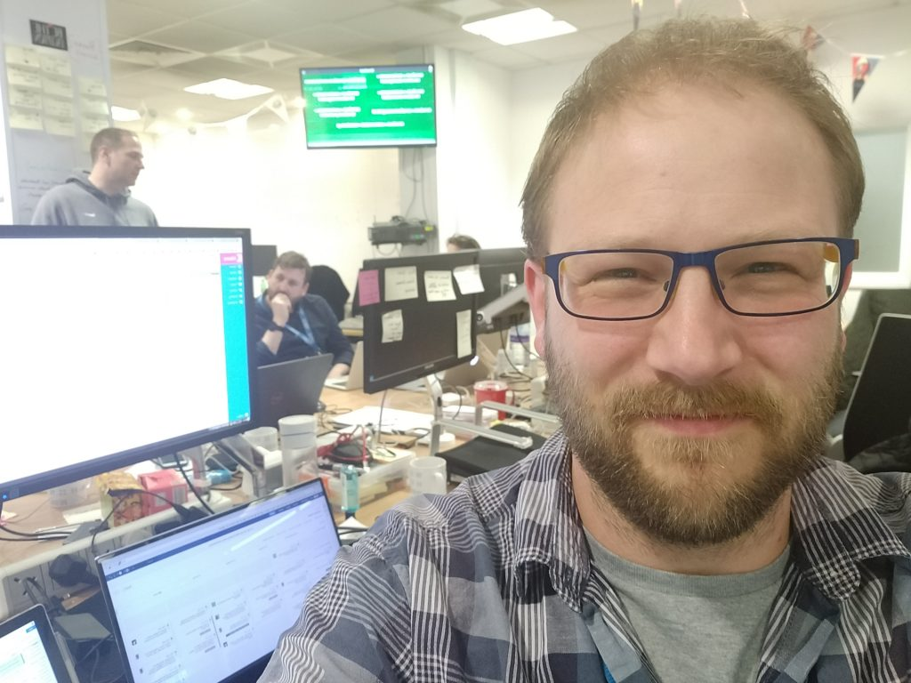 A selfie of Ben Conrad sitting in front of a screen in an open plan office