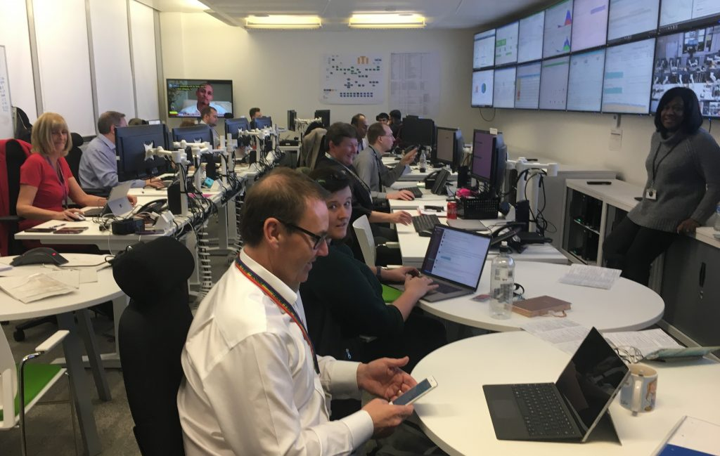 Teams of people in the Self Assessment Mission Control 2018. Two rows of desks looking at a wall with a bank of large screens