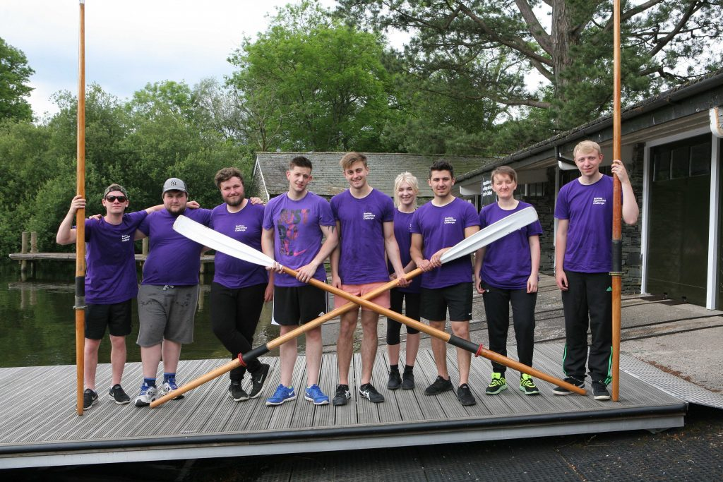 The Brathay challenge apprenties in purple tshirts standing on a jetty holding boat oars
