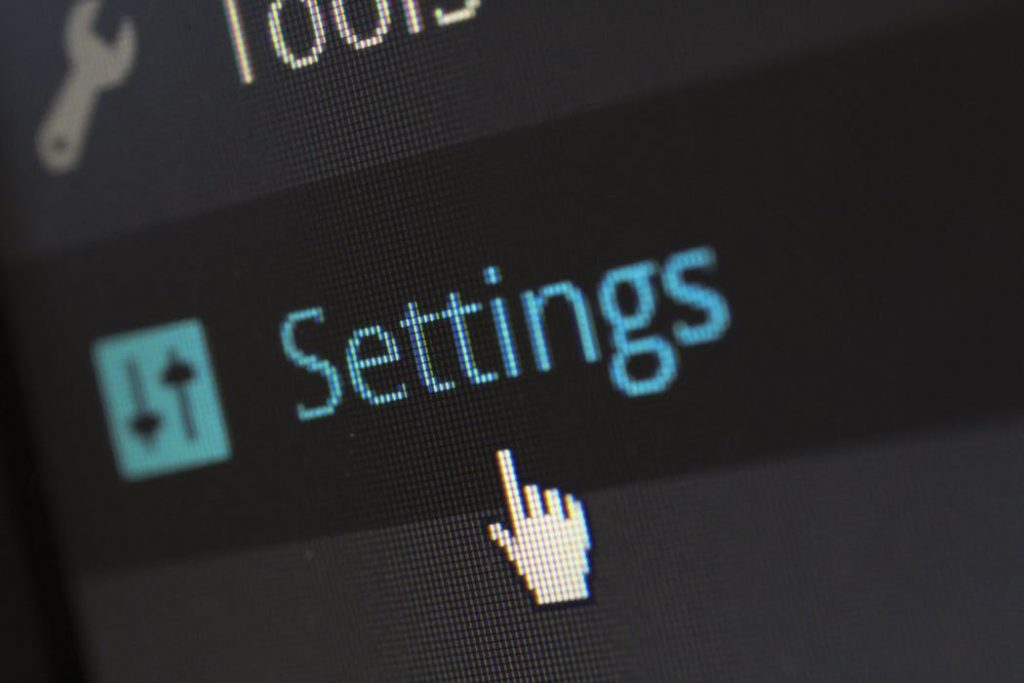 computer image of a hand pointing at the word settings