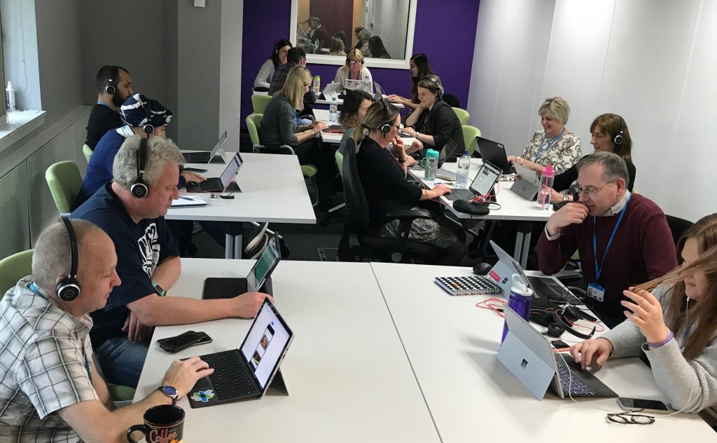 Image showing judges sitting at desks with headphones on looking at the apps on laptops