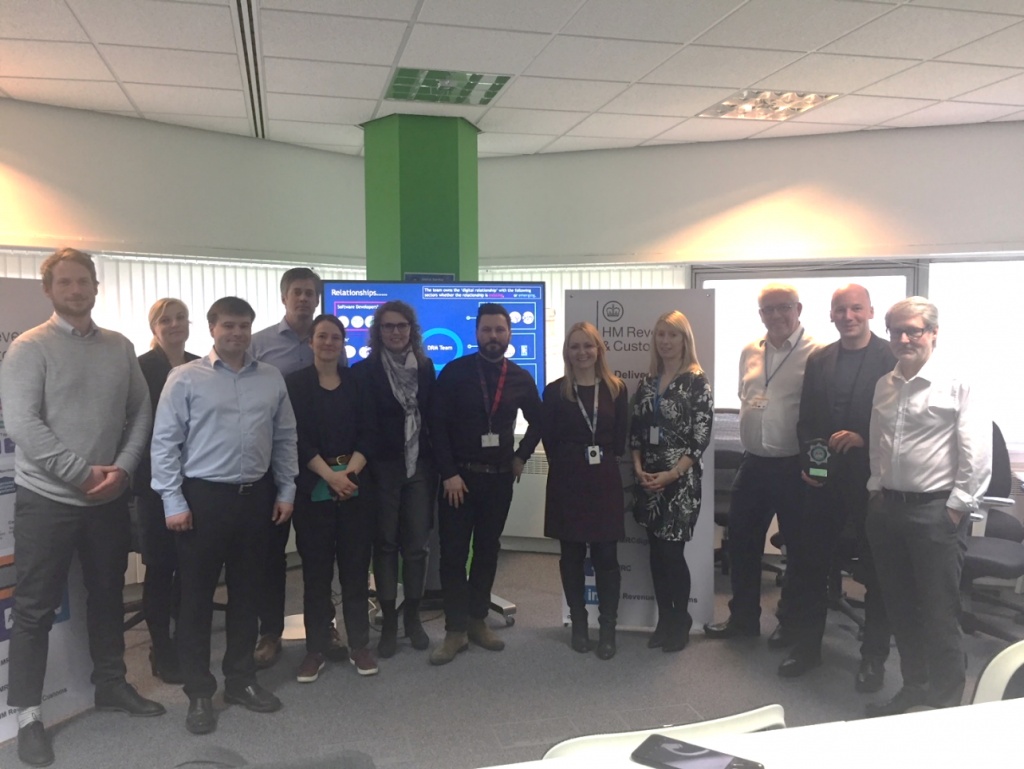 The Danish Tax Authority representatives and the team pose for a picture, standing in the office