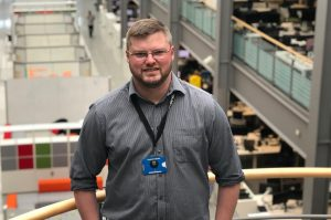 IT delivery manager Paul Shreeve standing on balcony with a large atrium and open plan office behind him
