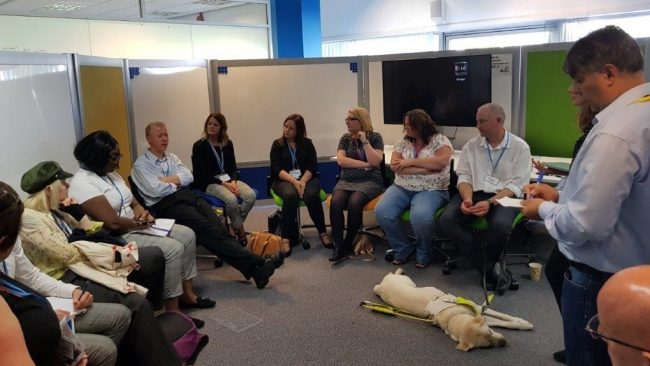 A group of delegates sitting in a circle having a discussion. A guide dog is asleep on the floor