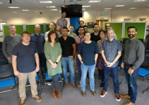The Developer Hub team stand in an open plan office to pose for a team photo