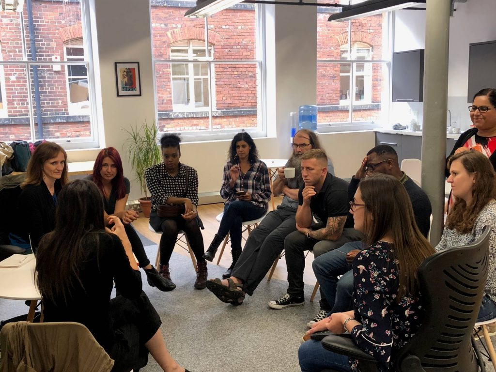 A group of user researchers sitting in a circle having an in depth discussion