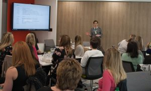 Chloe Walker presenting in front of an audience at Women in Digital