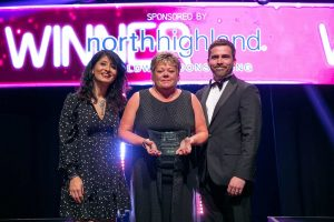 Margaret on stage at the UK IT Awards receiving her award from a male and female presenter