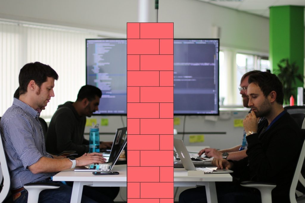 The dev ops team working on lap tops divided by a brick wall