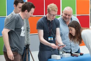 A group of five digital team members looking excitedly at a piece of tech kit in front of a brightly coloured background