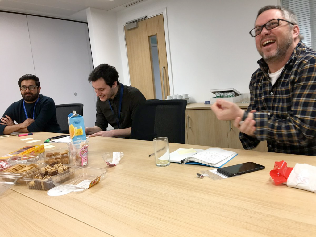 Three males at OneTeamGov sitting at a table laughing