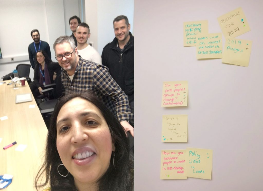 Seven people in a selfie shot and a wall of sticky notes from the session