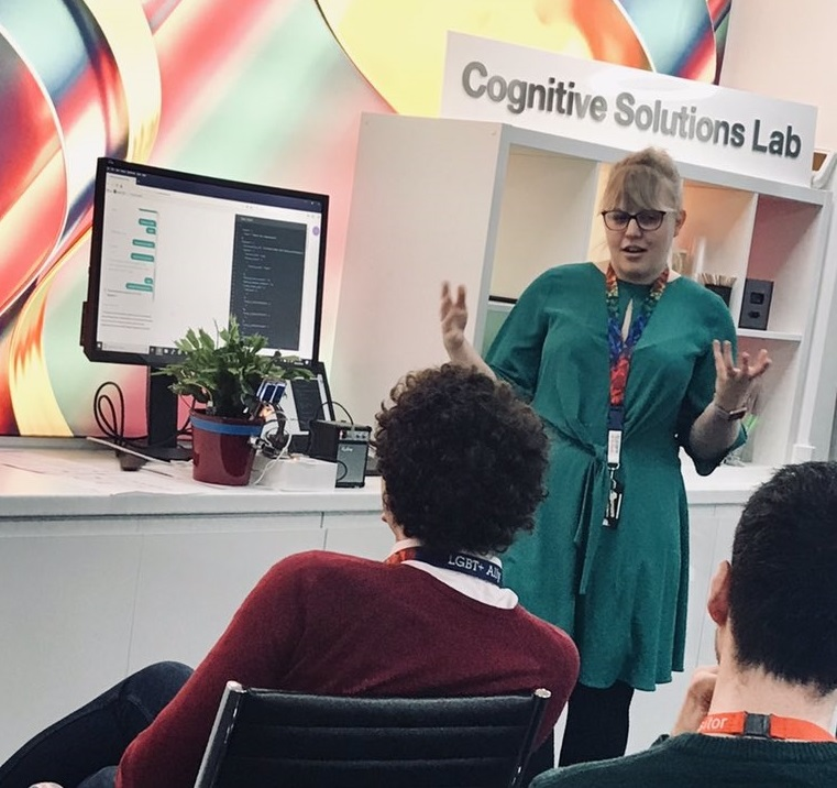 A female presenter is standing talking to her audience in a brightly coloured high tech office