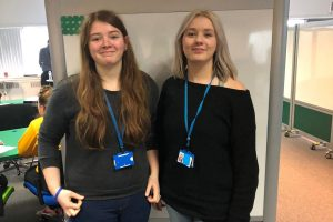 Two female apprentices standing in front of a screen