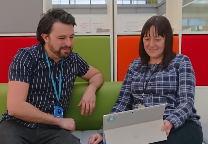 A male and female sitting on a colourful sofa looking at a laptop
