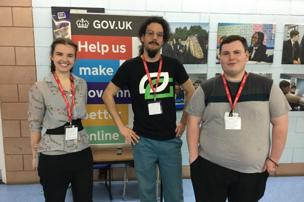 Jennifer McMillan, Louis Mannevy and Jack Witchell standing facing the camera in front of a gov.uk display board