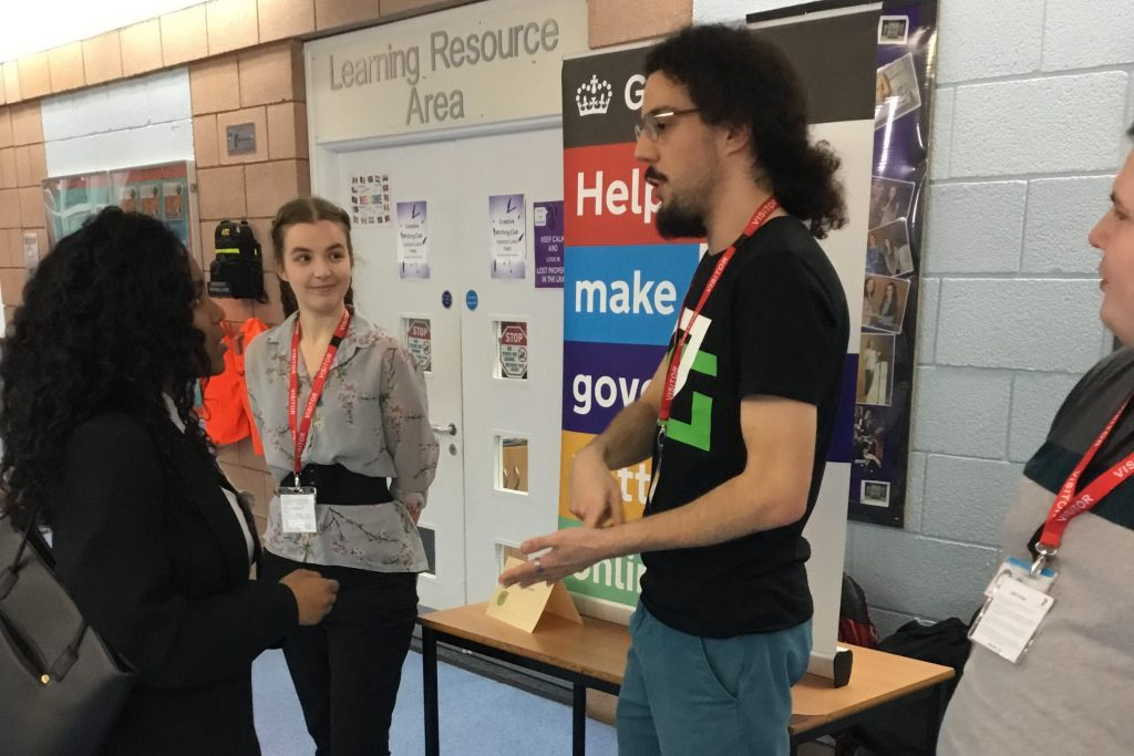 Louis Mannervy standing in front of the HMRC display talking to a female student