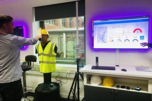 A male TechConnect participant trying out an IBM gadget in front of a large monitor