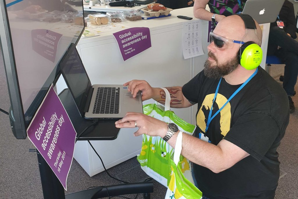 A man wearing blackout glasses and with his arms weighted by bags is trying to use an HMRC online service