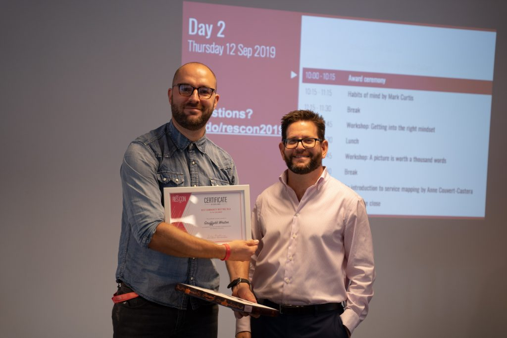 Image of two attendees, one presenting an award to the other